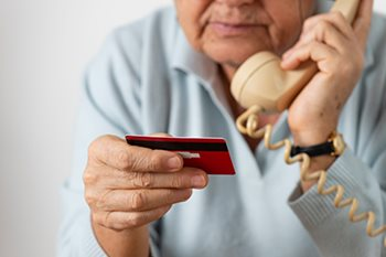 elderly person the phone with debit card in hand