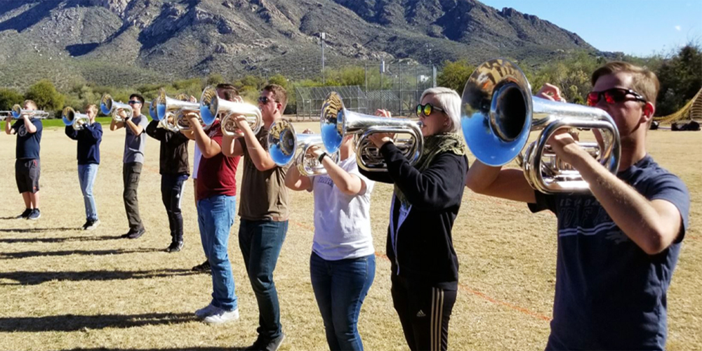 The Wolf Pack Marching Band Practices in Sectionals Outdoors